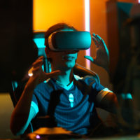 Positive young male gamer in tshirt sitting at table and using virtual reality simulator while playing video game